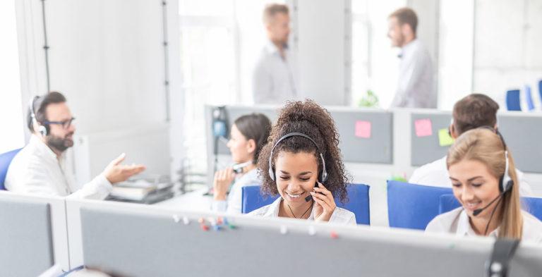 Mehrere Mitarbeiter im Callcenter vor Bildschirmen