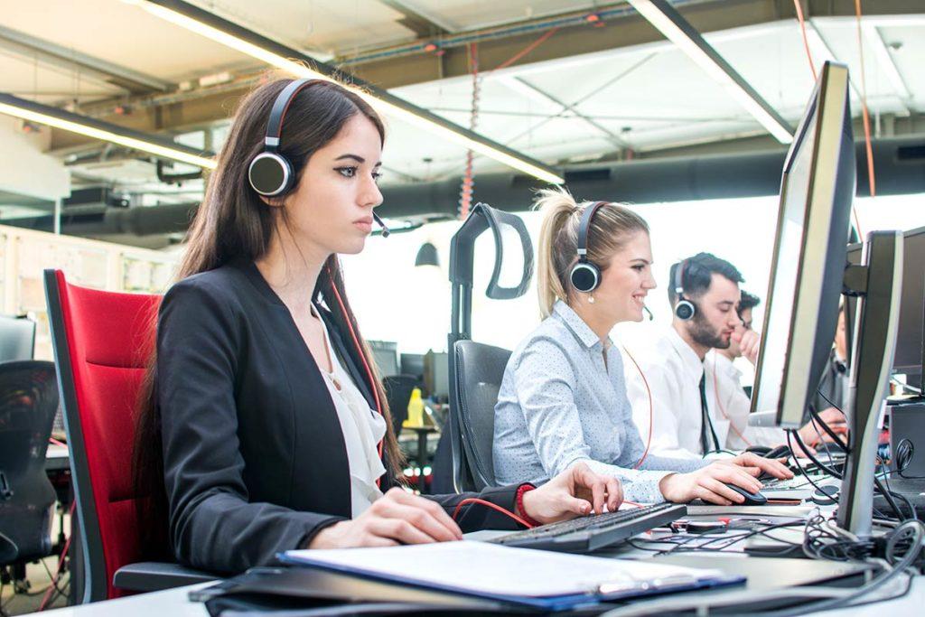 Zwei Frauen und ein Mann nebeneinander sitzend im Callcenter mit Headsets vor Bildschirmen