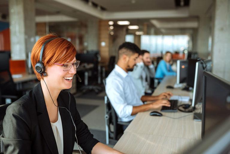 Frau mit Headset sitzt am Computer und telefoniert