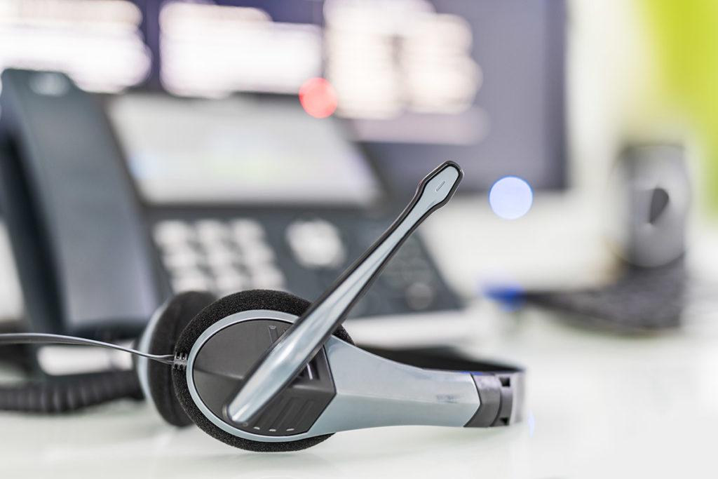 Headset im Vordergrund, Telefon und Computer unscharf im Hintergrund