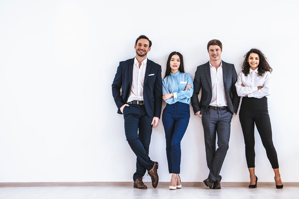 Vier Auszubildende im Business-Outfit lehnen an weißer Wand und schauen gut gelaunt zum Betracher.