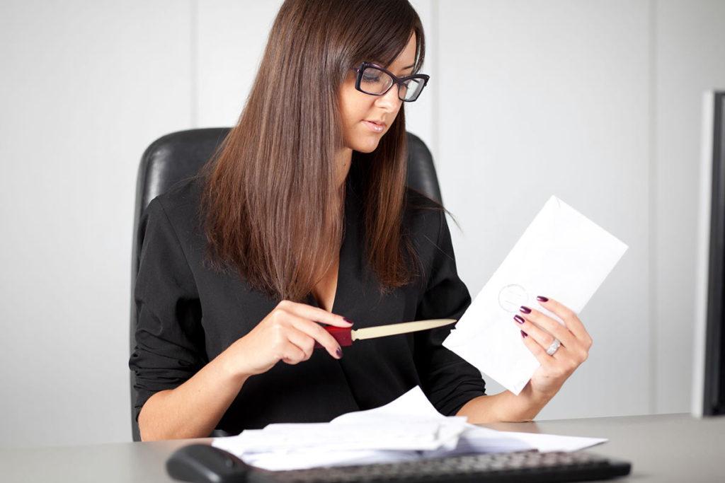 Frau im Büro am Schreibtisch öffnet Brief mit Brieföffner