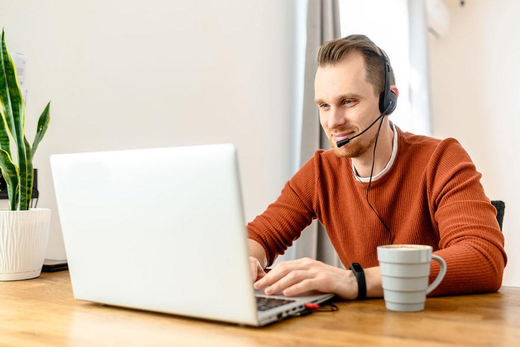 Mann am Schreibtisch vor Laptop mit Headset auf dem Kopf