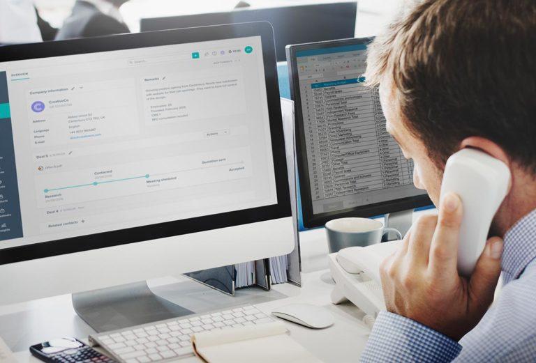 Callcenter-Agent mit Hörer am Ohr vor zwei Bildschirmen