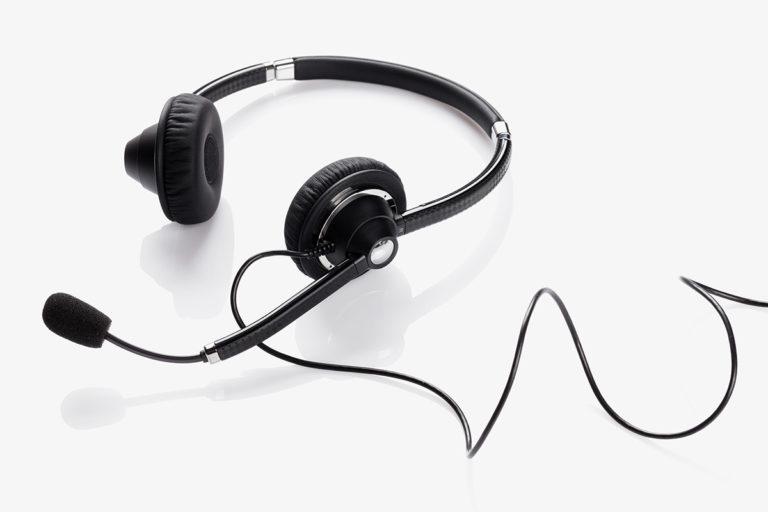 Kabelgebundener Kopfhörer mit Mikrofon auf weißer Tischplatte