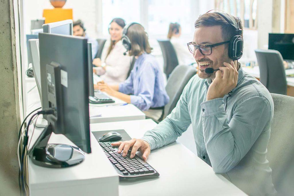 Männlicher Callcenter-Mitarbeiter freundlich telefonierend vor Computer