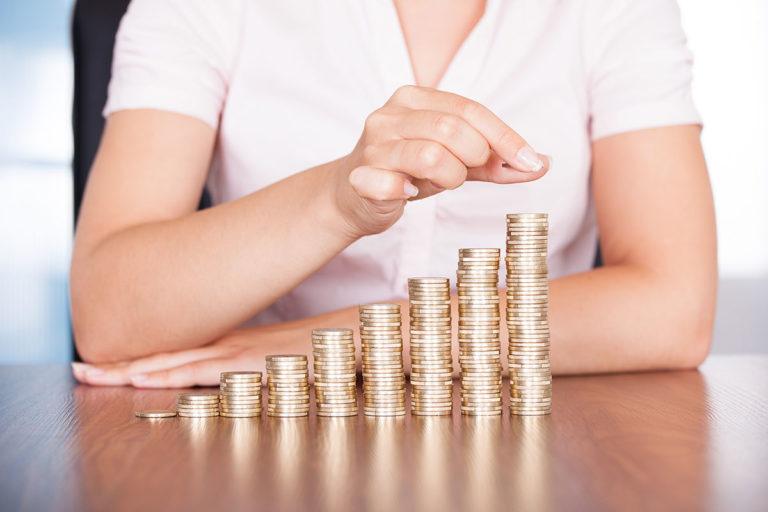 Frau stapelt Münzen vor sich auf