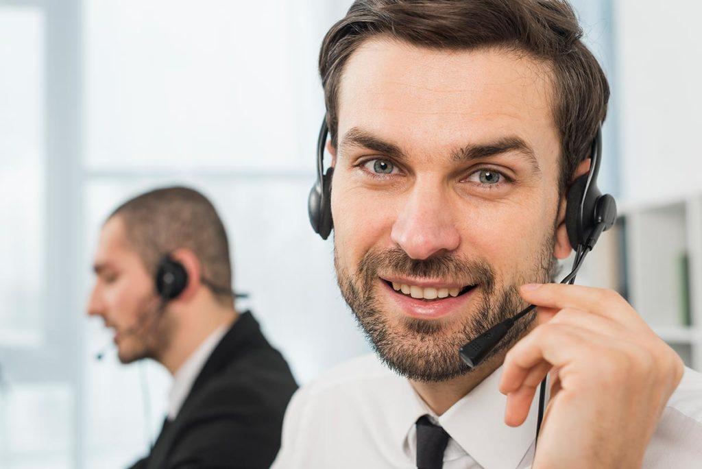 Männlicher Callcenter-Mitarbeiter mit Headset lächelt freundlich