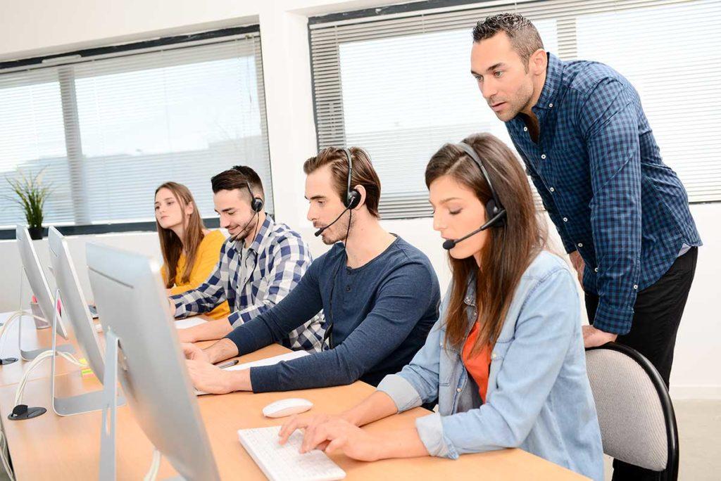 Callcenter-Agents vor ihren Computern, Schulungsleiter dahinterstehend