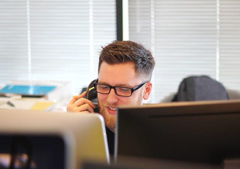 Junger Mann mit Telefonhörer am Ohr hinter zwei Bildschirmen im Callcenter