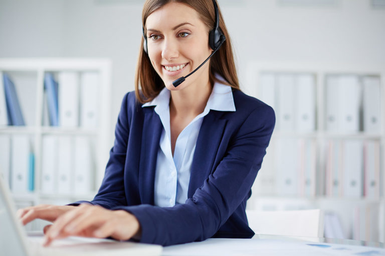 Frau im Büro im blauen Kostüm mit Headset am Computer tippend
