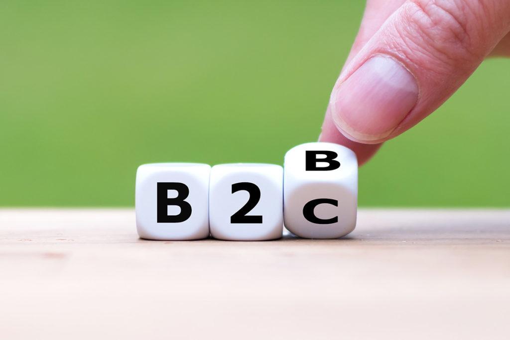 Drei Würfel nebeneinander auf einem Tisch, die ersten beide zeigen B und 2, der dritte wird mit Daumen und Zeigefinger von B auf C gedreht