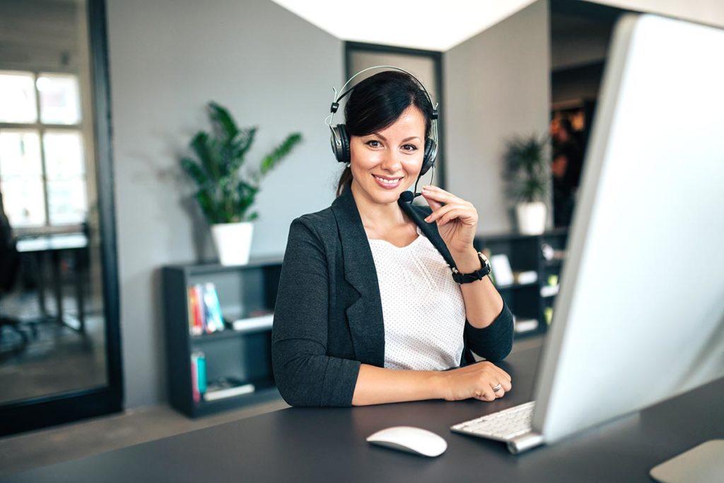 Frau mit Headset am Schreibtisch vor Computer allein in einem Büro.