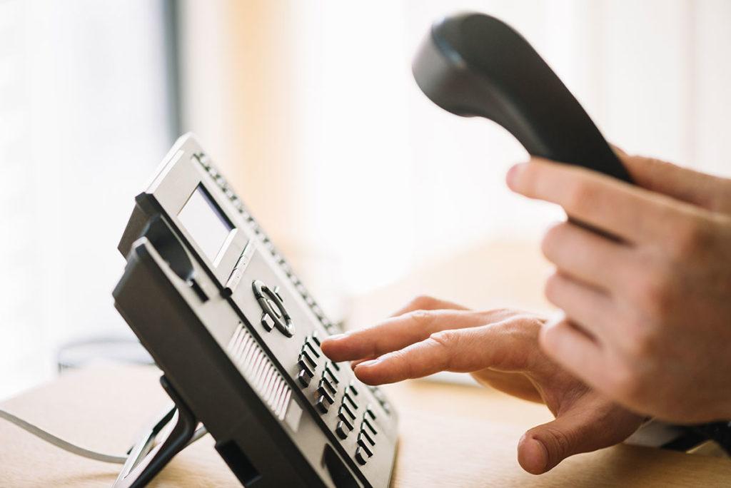 Telefon auf Tisch, Hörer mit der einen Hand abgenommen, mit der anderen Hand wählend